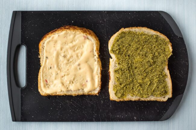 Slices of bread spread with pesto and mayonnaise.