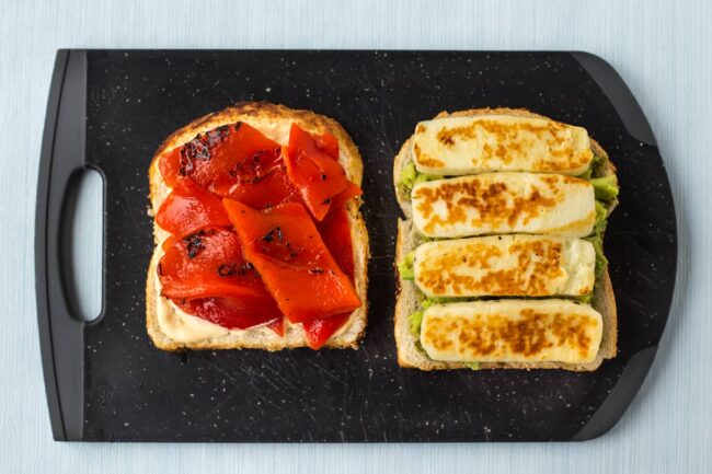 A sandwich being made on a board with fried halloumi and roasted red peppers.