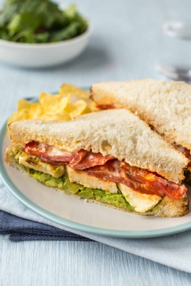 A sandwich filled with fried halloumi, roasted red peppers and mashed avocado.