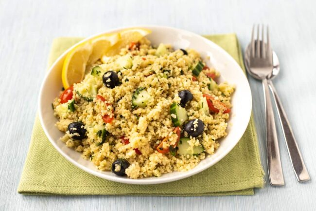 Couscous salad in a bowl with black olives and cucumbers.