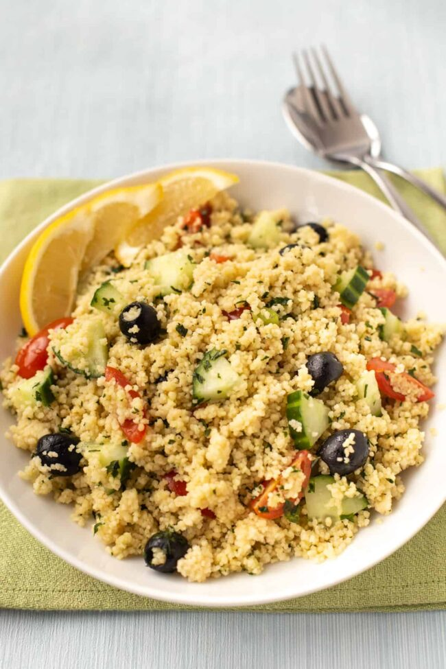 Couscous salad with black olives, cucumber, tomatoes, and lemon slices.