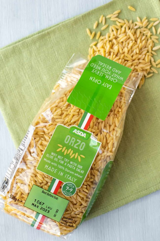 A packet of orzo spilling orzo onto a green linen.