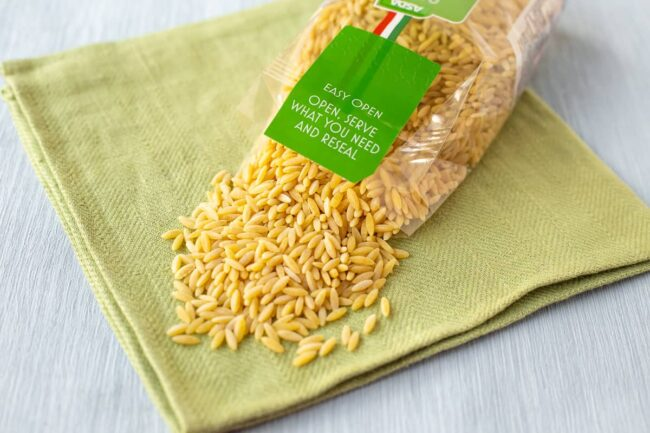 A packet of orzo spilling pasta onto a green linen.