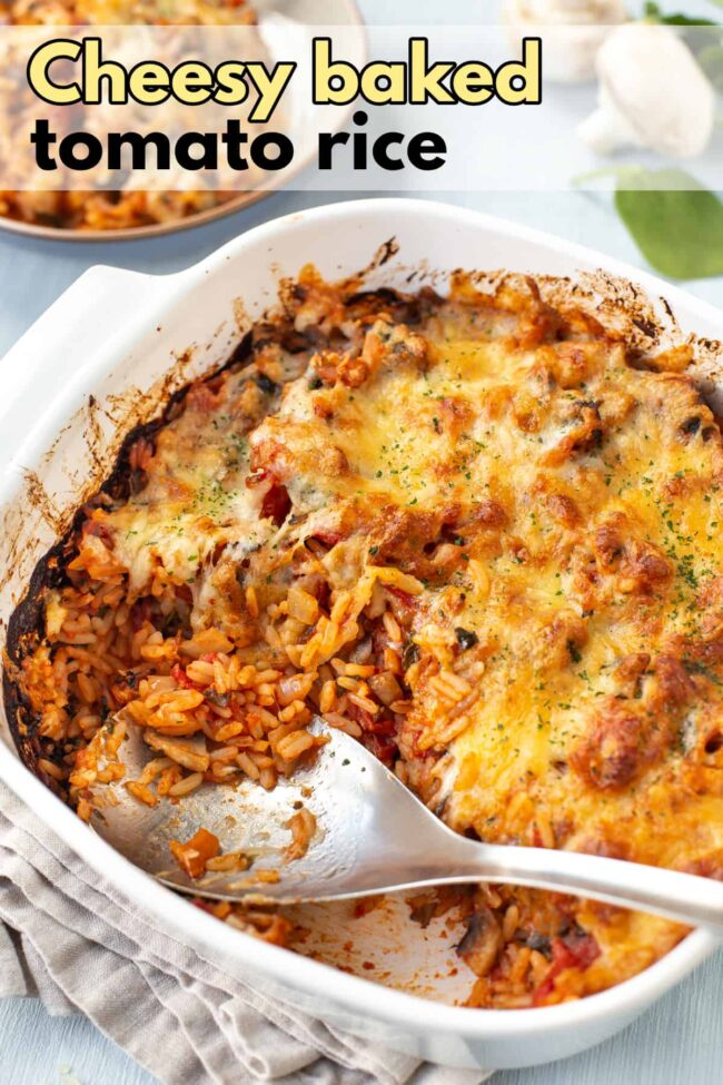 Baked tomato rice in a baking dish with a cheesy topping.