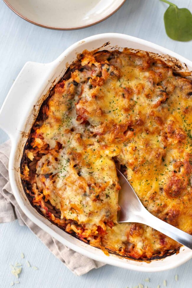 A dish full of baked tomato rice with a gooey cheese topping.