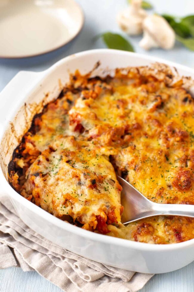 A cheesy rice bake in a dish, with a large spoon scooping it.