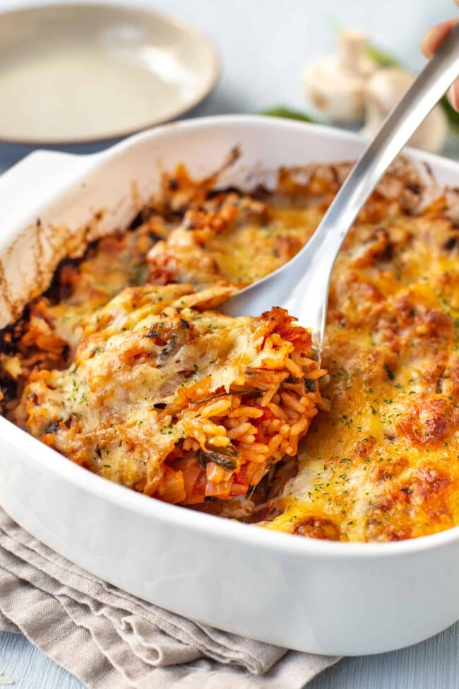 A large spoon scooping into a dish of cheesy baked tomato rice.