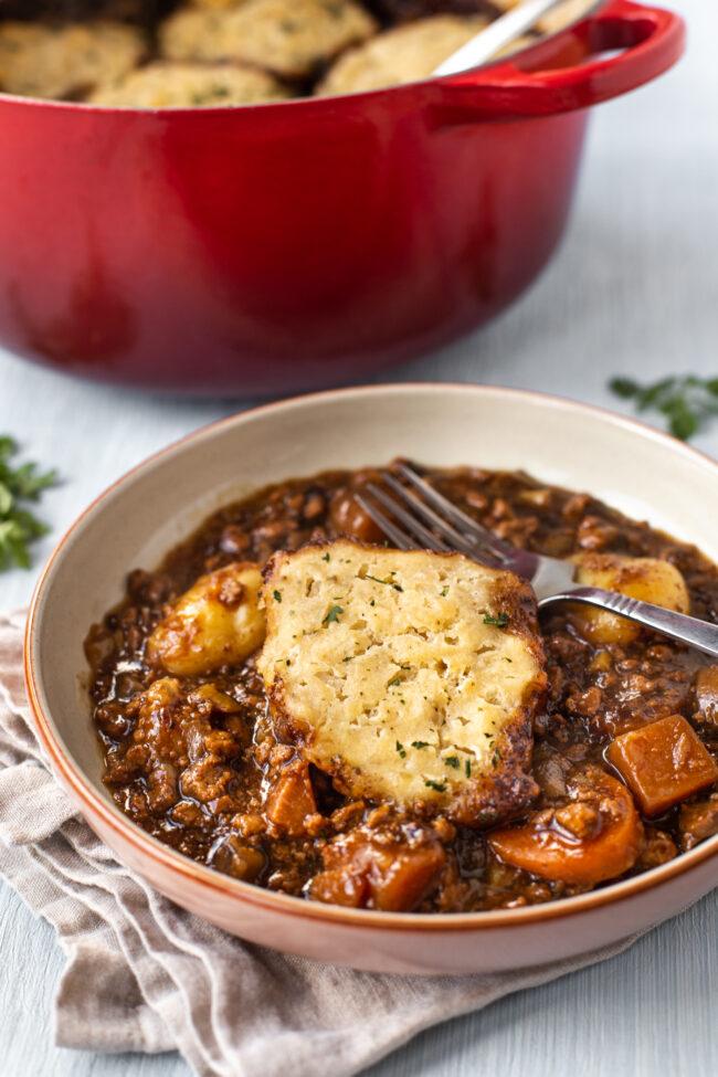 A bowl of vegetarian stew with a suet dumpling.