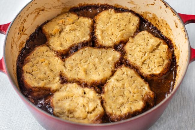 Crispy suet dumplings on top of a pot of stew.